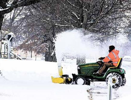 Travis Karbowksi of the Pawnee Village maintenance staff clears sidewalks Monday. Ray Kappel/Republican